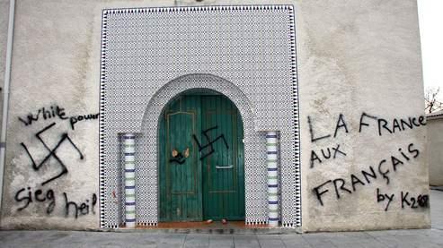 Vue prise le 13 décembre 2009, de la façade de la mosquée de Castres qui a été profanée dans la nuit par des inconnus qui ont taggé sur ses murs des propos xénophobes et des croix gammées. Des pieds de cochon ont également été suspendus à la poignée du portail. Sur la porte, des oreilles de cochon avaient été agrafées et des affiches placardées sur lesquelles étaient dessinés des drapeaux français, a précisé le président de l'Association islamique de Castres, Abdelmalek Bouregba.   AFP PHOTO / THIERRY ANTOINE