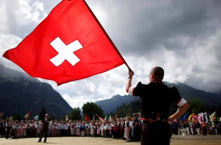 A boy dressed in traditional a costume waves a Swiss flag during the official ceremonial act at the 28th Federal Yodelling Festival in Interlaken